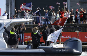 Photo - Fans cheer as a boat carrying Oracle CEO Larry Ellison passes a pier after Oracle Team USA defeated Emirates Team New Zealand in the 18th race of the America's Cup sailing event Tuesday, Sept. 24, 2013, in San Francisco. Oracle Team USA won both races Tuesday to even the series. (AP Photo/Ben Margot)