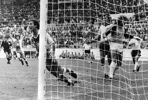 Photo - FILE - In this June 16, 1982 file photo, Algeria's Lakhdar Belloumi, left, celebrates after scoring the second and winning goal for his team during the World Cup soccer match between Algeria and West Germany in Gijon, Spain. On this day: Algeria beats West Germany 2-1 in one of the great upsets in World Cup history. (AP Photo/File)