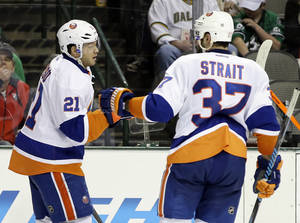 Photo - New York Islanders right wing Kyle Okposo (21) is congratulated on his goal against the Dallas Stars by Brian Strait (37) in the second period of an NHL hockey game, Sunday, Jan. 12, 2014, in Dallas. (AP Photo/Tony Gutierrez)