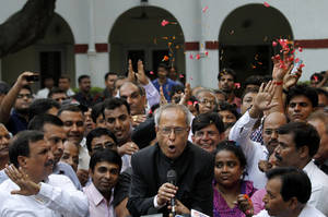 Photo -   Relatives throw flower petals as India's president elect Pranab Mukherjee addresses media outside his residence after winning the election in New Delhi, India, Sunday, July 22, 2012. The candidate from India's governing Congress party, former Finance Minister Mukherjee, was declared winner Sunday in the election for the country's next president, a largely ceremonial position. (AP Photo/ Manish Swarup)