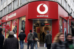 Photo - FILE - In this Tuesday, Feb. 24, 2009 file photo, people walk by a Vodafone branch in central London. Vodafone, one of the world's largest cellphone companies, on Friday, June 6, 2014 revealed the scope of government snooping into phone networks, saying authorities in some countries are able to directly access an operator's network without seeking permission. (AP Photo/Sang Tan, File)
