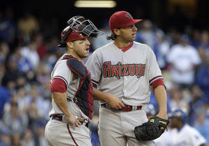 Photo - Arizona Diamondbacks starting pitcher Mike Bolsinger, right, and catcher Miguel Montero look at the scoreboard during the fifth inning of a baseball game against the Los Angeles Dodgers, Saturday, April 19, 2014, in Los Angeles. (AP Photo/Jae C. Hong)