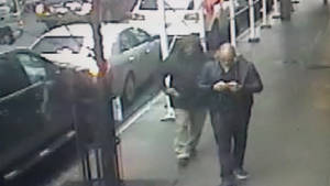 photo - This still image made from a video provided by the New York City Police Department shows the gunman, left, behind Brandon Lincoln Woodard pulling the weapon from his jacket pocket a moment before the shooting, Mon. Dec. 10, 2012 in New York. A security camera photo shows a man pulling a weapon from his pocket moments before police say he shot a Los Angeles man in midtown Manhattan. The NYPD released the photo Tuesday amid a manhunt for the unidentified suspect in the execution-style slaying (Ap Photo/New York Police Department/ HO)