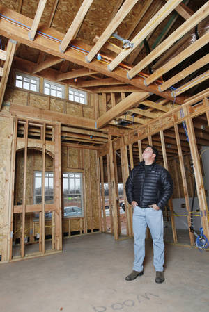 Photo - Homebuilder Caleb McCaleb looks at the sprinkler system he's installing.