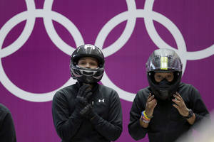 Photo - Jazmine Fenlator, right, and Lolo Jones of the United States prepare for a heat race of the women's bobsleigh competition at the 2014 Winter Olympics,  Friday, Feb. 14, 2014, in Krasnaya Polyana, Russia. (AP Photo/Michael Sohn)