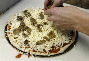 Photo -  Brian Scritchfield adds mushrooms to a small pizza ordered at Bobtown Pizza in Bobtown, Pa. AP Photo  <strong>Keith Srakocic -  AP </strong>