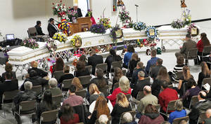 Photo - Friends and family members look on at the caskets of Summer Rust and her four children, Kirsten, Autumn and Teagin Rust and Evynn Garas, in El Reno on Wednesday. PHOTOS BY CHRIS LANDSBERGER, THE OKLAHOMAN