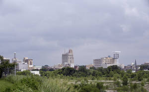Photo - In a June 12, 2014 photo in Flint, Mich., the skyline of the city is seen from the west side. As Detroit hopes to ride out of bankruptcy this year, a smaller Michigan city with a similarly strong bond to the automotive industry soon could drive in. Flint, like its bankrupt big brother an hour's drive south, has suffered a spectacular drop in population and factory jobs with a corresponding rise in property abandonment and crime. (AP Photo/Carlos Osorio)