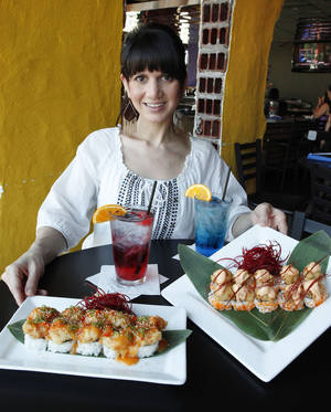 Photo - Anna Mains, In The Raw Sushi managing partner, shows some of the restaurant's Thunder themed menu items. <strong>David McDaniel - The Oklahoman</strong>
