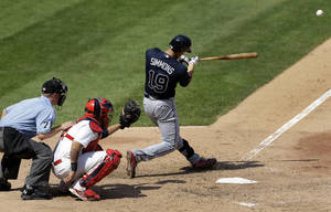 Photo - Atlanta Braves' Andrelton Simmons, right, hits a solo home run as St. Louis Cardinals catcher Yadier Molina, center, and home plate umpire Mike Muchlinski, left, watch during the seventh inning of a baseball game on Sunday, Aug. 25, 2013, in St. Louis. (AP Photo/Jeff Roberson)