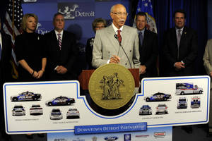 """Photo - Detroit Mayor Dave Bing, center, unveils an ambitious plan by local business leaders to fund the purchase of public safety vehicles for the cash-strapped city, on Monday, March 25, 2013. In what was described as an """"unprecedented collaboration,"""" Bing held a press conference with industrialist Roger Penske to announce the plan that included an $8 million donation for the leasing of 23 new EMS vehicles and 100 police cruisers. A separate $6 million has also been committed for recreation programming in the city, with $5 million from Lear Corp. and $1 million from DTE Energy Co. (AP Photo/The  Detroit News, David Coates)"""