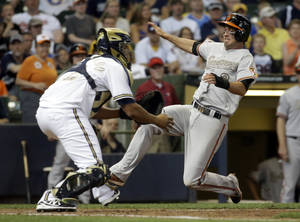 Photo - Baltimore Orioles' J.J. Hardy scores past Milwaukee Brewers catcher Martin Maldonado during the 10th inning of a baseball game Monday, May 26, 2014, in Milwaukee. Hardy scored from second on a hit by Nick Hundley. (AP Photo/Morry Gash)