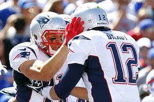 Photo - New England Patriots' Julian Edelman, left, celebrates with teammate Tom Brady, right, after catching a touchdown pass during the first half of an NFL football game against the Buffalo Bills, Sunday, Sept. 8, 2013, in Orchard Park. (AP Photo/Bill Wippert)