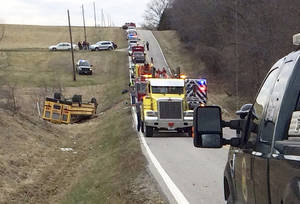 Photo - A tow truck, fire truck and emergency response personnel work on the scene of an overturned school bus near the rural northeast town of Ewing, Mo., Tuesday, April 1, 2014. Authorities say nearly two dozen students were injured in the accident. (AP Photo/Quincy Herald Whig/Steve Bohnstedt)