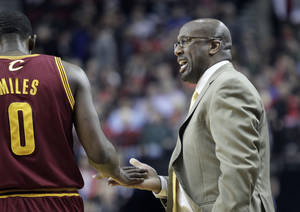 Photo - Cleveland Cavaliers coach Mike Brown, right, slaps hands with Cleveland Cavaliers guard C.J. Miles during the first half of an NBA basketball game in Portland, Ore., Wednesday, Jan. 15, 2014. (AP Photo/Don Ryan)