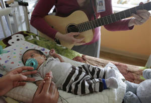 Photo - Music therapist Elizabeth Klinger, right, quietly plays guitar and sings for Augustin as he grips the hand of his mother, Lucy Morales, in the newborn intensive care unit at Ann & Robert H. Lurie Children's Hospital in Chicago on Monday, May 6, 2013. Research suggests that music may help those born way too soon adapt to life outside the womb. Recent studies and anecdotal reports suggest the vibrations and soothing rhythms of music, especially performed live in the hospital, might benefit preemies and other sick babies. (AP Photo/M. Spencer Green)