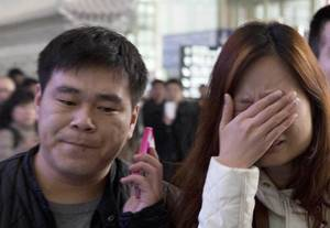 Photo - ALTERNATE CROP OF XHG102 A woman cries at the arrival hall of the International Airport in Beijing, China, Saturday, March 8, 2014. Relatives and friends were arriving at Beijing airport for news after a Malaysia Airlines Boeing 777-200 was reported missing on a flight from Kuala Lumpur to Beijing Saturday. (AP Photo/Ng Han Guan)