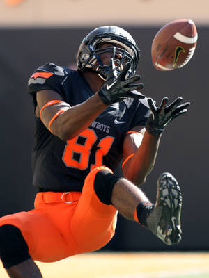 Photo - Oklahoma State wide receiver Jhajuan Seales catches a 43-yard pass from quarterback J.W. Walsh during the first half of an NCAA college football game against Kansas State in Stillwater, Okla., Saturday, Oct. 5, 2013. (AP Photo/Brody Schmidt)