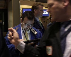 "photo - FILE - Trader Richard Scardino, left, works on the floor of the New York Stock Exchange, in this Dec. 14, 2012 file photo taken in in New York. World stock markets faced resistance Thursday Dec. 20, 2012 after talks turned sour among U.S. political leaders trying to reach an agreement over how to avert an economically disastrous ""fiscal cliff"" before the end of the year. A downturn in U.S. housing starts also hurt sentiment.  (AP Photo/Richard Drew, File)"