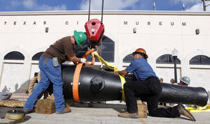 Photo - Jimmy Yancey, left, and Rene Del Bosque, both with Domac Inc., secure strapping around the the 11-foot long, 8,400 pound Dahlgren gun as they move it to the Texas City Museum on Wednesday June 18, 2014, in Texas City, Texas.  A Civil War cannon from the 1863 sinking of the USS Westfield has a new resting place at a Texas museum just miles from where the ship went down.   Officials at the Texas City Museum on Wednesday welcomed the restored 12-foot cannon for a maritime exhibit. (AP Photo/The Galveston County Daily News, Jennifer Reynolds) MANDATORY CREDIT; MAGS OUT; TV OUT