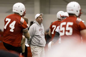 photo - Nebraska head coach Bo Pelini, center, follows the first day of spring NCAA college football practice in Lincoln, Neb., Saturday, March 2, 2013. (AP Photo/Nati Harnik)
