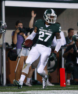 Photo - Michigan State's Kurtis Drummond scores a touchdown on an interception return during the first quarter of an NCAA college football game against Western Michigan, Friday, Aug. 30, 2013, in East Lansing, Mich. The ball was intercepted by Jairus Jones and lateraled to Drummond for the score. (AP Photo/Al Goldis)