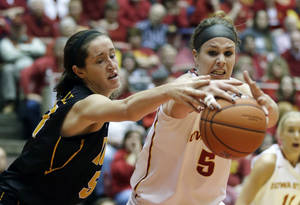 Photo - Iowa center Bethany Doolittle, left, fights for a rebound with Iowa State forward Hallie Christofferson during the first half of an NCAA college basketball game, Thursday, Dec. 12, 2013, in Ames, Iowa. (AP Photo/Charlie Neibergall)