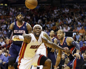 photo - Miami Heat's LeBron James (6) forces Atlanta Hawks' Dahntay Jones (30) away from the ball during the first half of an NBA basketball game in Miami, Tuesday, March 12, 2013. (AP Photo/J Pat Carter)