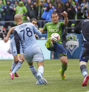 Photo - Seattle Sounders forward Chad Barrett kicks a goal at short range against Sporting Kansas City goalkeeper Eric Kronberg, right, during stoppage time in the second half of an MLS soccer match, Saturday, March 8, 2014, in Seattle. The Sounders beat Sporting KC 1-0. (AP Photo/Ted S. Warren)