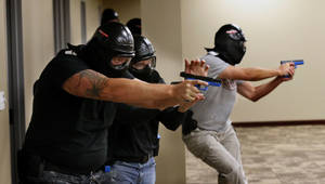 Photo - Law enforcement officers armed for combat confront a shooter Tuesday in a role-playing, training exercise at the Moore Norman Technology Center.