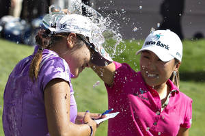 Photo - Lydia Ko, left, of New Zealand, is doused by I.K. Kim, of South Korea, after winning the LPGA Canadian Women's Open golf tournament in Edmonton, Alberta, Sunday, Aug. 25, 2013. (AP Photo/The Canadian Press, Jason Franson)