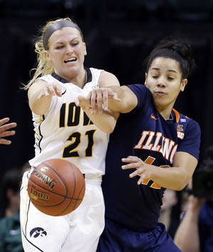 Photo - Illinois guard Amber Moore, right, knocks the ball away from Iowa guard Melissa Dixon in the second half of an NCAA college basketball game in the opening round of the Big Ten Tournament in Indianapolis, Ind., Thursday, March 6, 2014. Iowa won 81-62. (AP Photo/Michael Conroy)