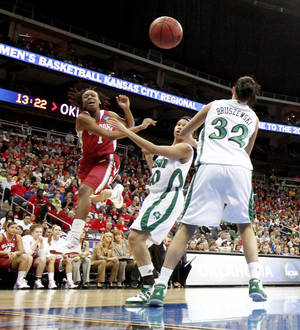 Photo - OU's Nyeshia Stevenson passes the ball over Notre Dame's Ashley Barlow, left, and Becca Bruszewski during the Sweet 16 round of the NCAA women's  basketball tournament in Kansas City, Mo., on Sunday, March 28, 2010. Photo by Bryan Terry, The Oklahoman
