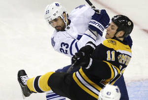 Photo - Toronto Maple Leafs defenseman Ryan O'Byrne (23) checks Boston Bruins center Gregory Campbell (11) during the first period in Game 5 of an NHL hockey Stanley Cup playoff series in Boston, Friday, May 10, 2013. (AP Photo/Charles Krupa)