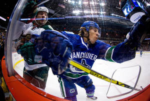 Photo - Vancouver Canucks' David Booth, right, misses the check on Minnesota Wild's Keith Ballard and crashes into the glass during the first period of an NHL hockey game Friday, Feb. 28, 2014, in Vancouver, British Columbia. (AP Photo/The Canadian Press, Darryl Dyck)