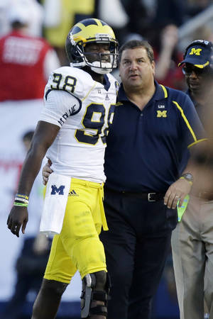 Photo - Michigan head coach Brady Hoke, right, talks with Michigan quarterback Devin Gardner (98) during the second quarter an NCAA college football game against Penn State in State College, Pa., Saturday, Oct. 12, 2013. (AP Photo/Gene J. Puskar)