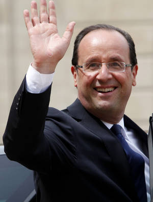 Photo -   New President Francois Hollande waves as he leaves the Elysee Palace Tuesday, May 15, 2012 in Paris. (AP Photo/Thibault Camus)
