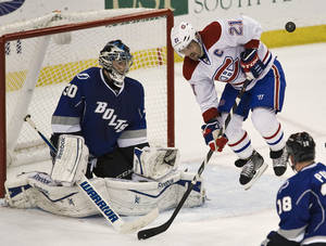 Photo - Montreal Canadiens' Brian Gionta (21) leaps away from a shot on goal as he blocks Tampa Bay Lightning's Ben Bishop (30) during the second period of an NHL hockey game Saturday, Dec. 28, 2013, in Tampa, Fla. (AP Photo/Steve Nesius)