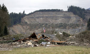 Photo - A flag, put up by volunteers helping search the area, stands in the ruins of a home left at the end of a deadly mudslide from the now-barren hillside seen about a mile behind, Tuesday, March 25, 2014, in Oso, Wash. At least 14 people were killed in the 1-square-mile slide that hit in a rural area about 55 miles northeast of Seattle on Saturday. Several people also were critically injured, and homes were destroyed. (AP Photo/Elaine Thompson)