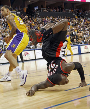 Photo -   Portland Trail Blazers forward J.J. Hickson, right, goes flying after colliding with Los Angeles Lakers center Robert Sacre in an NBA basketball preseason game in Ontario, Calif., Wednesday, Oct. 10, 2012. (AP Photo/Reed Saxon)
