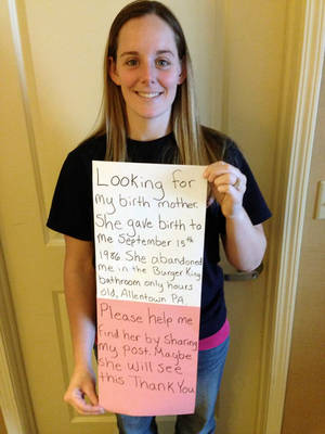 Photo - This March 2, 2014 photo provided by Katheryn Deprill that she posted on Facebook, shows her holding a sign that says she is seeking her birth mother. Deprill was abandoned in the bathroom of a Burger King restaurant in Allentown, Pa., when she was a few hours old. (AP Photo/Courtesy of Katheryn Deprill)