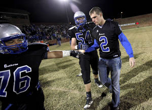 Photo - Guthrie's Malachai Galbraith, left, and Blake Belcher greet Clint Simek, right, after the coin toss for their high school football game against Southeast in Guthrie, Friday, Nov. 4, 2011. The Oklahoma Secondary School Activities Association has ruled that Guthrie has fielded an ineligible player and will be forced to forfeit eight of its nine wins this season. Photo by Bryan Terry, The Oklahoman