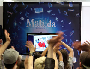 "Photo - This May 7, 2013 photo shows the cast of the Tony Award-nominated ""Matilda"" waving to Tim Marshburn, one of six astronauts aboard the International Space Station, via a satellite hook-up provided by NASA, at a gathering in New York. Cast members, including many children, packed a small room near Times Square on Tuesday to ask questions about life in space.  (AP Photo/Mark Kennedy)"