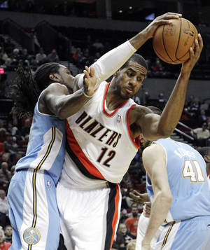 Photo -   Portland Trail Blazers forward LaMarcus Aldridge (12) pulls in a rebound against Denver Nuggets forward Kenneth Faried, left, and center Kosta Koufos (41), of Russia, during the first half of their preseason NBA basketball game in Portland, Ore., Wednesday, Oct. 17, 2012. (AP Photo/Don Ryan)