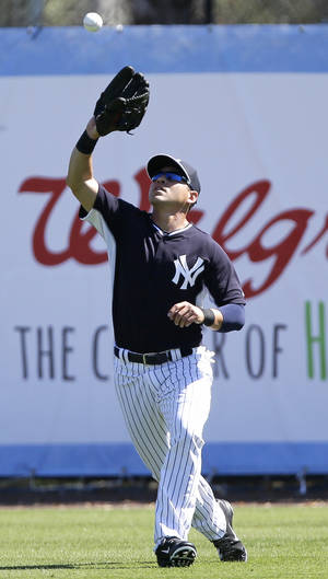 Photo - New York Yankees center fielder Jacoby Ellsbury catches a fly ball during spring training baseball practice Thursday, Feb. 20, 2014, in Tampa, Fla. (AP Photo/Charlie Neibergall)