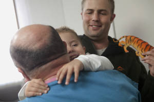 photo - Andre de Guisti, 2, from Johannesburg, South Africa, hugs Dr. Anthony de Bari on Wednesday, Jan. 9, 2013 at Covenant HealthCare in Saginaw, Mich. Dr. de Bari operated on de Guisti two years ago when he heard from a fellow doctor who traveled to South Africa for a hunting trip about a boy born with an abnormal development of the lower spine. Doctors in South Africa said the only option was to amputate Andre's legs, but when Dr. de Bari, who has three patients in Saginaw with the same condition, heard about Andre, he offered to help. The de Guistis flew to Saginaw and Andre received surgery the same week. Despite a lot of physical therapy ahead of him de Bari is surprised at how well Andre has improved and expects him to be able to walk. (AP Photo/The Saginaw News, Clay Lomneth )