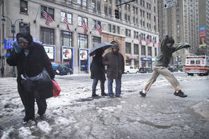 Photo - Pedestrians attempt to traverse slush puddles near Pennsylvania Station, Thursday, Feb. 13, 2014, in New York. Snow and sleet are falling on the East Coast, from North Carolina to New England, a day after sleet, snow and ice bombarded the Southeast. (AP Photo/John Minchillo)