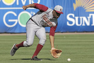Photo - Florida State's Jameis Winston picks up a sixth inning single by New York Yankees' Pete O'Brien a spring training exhibition game against the New York Yankees Tuesday, Feb. 25, 2014, in Tampa, Fla. Winston is the 2013 Heisman Trophy winner. (AP Photo/Chris O'Meara)