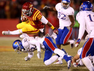 Photo - Iowa State running back Shontrelle Johnson (21) hurdles Kansas safety Cassius Sendish (33) during the first half of an NCAA college football game in Ames, Iowa, Saturday Nov. 23, 2013. (AP Photo/Justin Hayworth)