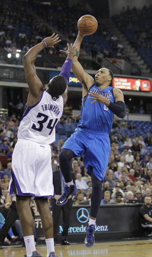 Photo - Dallas Mavericks forward Shawn Marion, right, shoots over Sacramento Kings forward Jason Thompson during the first quarter of an NBA basketball game in Sacramento, Calif., Friday, April 5, 2013. (AP Photo/Rich Pedroncelli)
